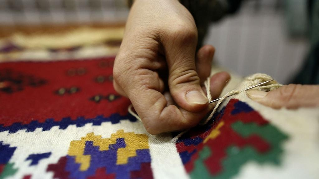 Den falska mattförsäljaren uppger att det är handvävda mattor. Foto: Darko Vojinovic / TT.