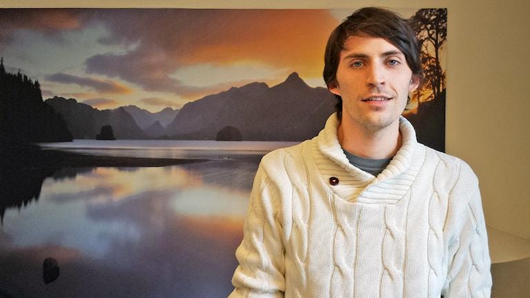 Per Hydén med kort brunt hår, vit tröja. Bakgrunden är en tavla med naturmotiv.