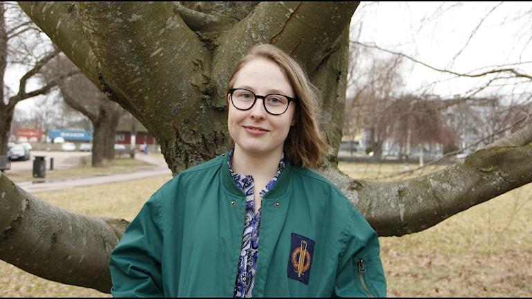 Ung ljushyad person med halvlångt blont hår, runda glasögon och en grön jacka. Står framför en trädstam. Beskuren så att överkroppen är med i bild.