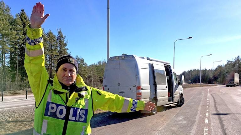 en trafikpolis vinkar in en bil