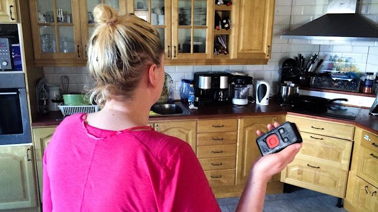 Pia Holm står i sitt kök med personlarmet i handen.