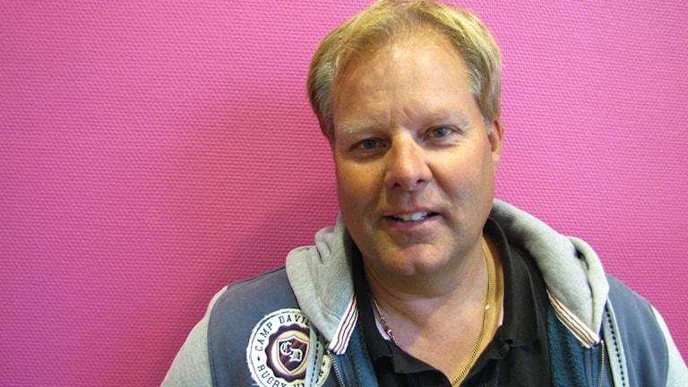 """Jan """"Flash"""" Nilsson står framför den rosa väggen på P4 Värmland."""