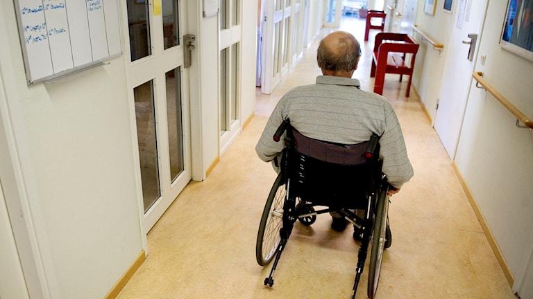 En äldre man sitter i en rullstol i en korridor. Foto: Jessica Gow/TT