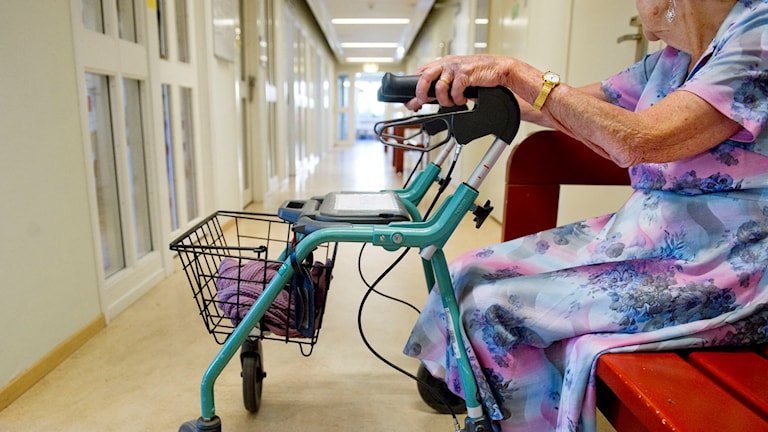 En äldre kvinna med rollator sitter på en bänk i en korridor. Foto: Jessica Gow/TT
