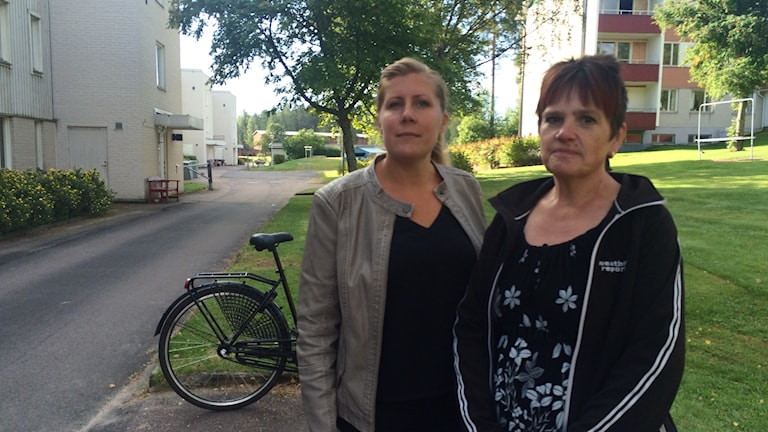 Två kvinnor framför hyreshus