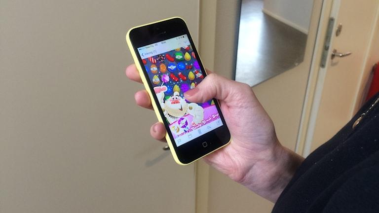 en hand håller mobil med candycrush på inomhus foto: annika stöm