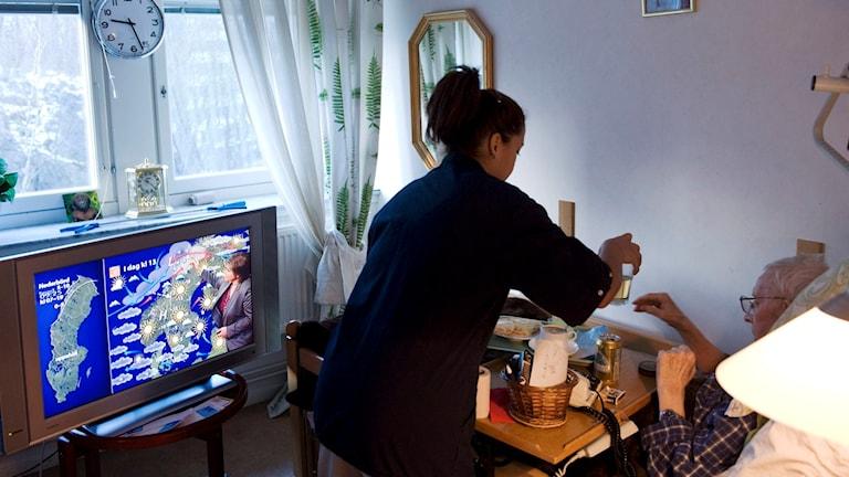 Vårdbiträde hjälper äldre kvinna med måltid. Foto: Henrik Montgomery/TT