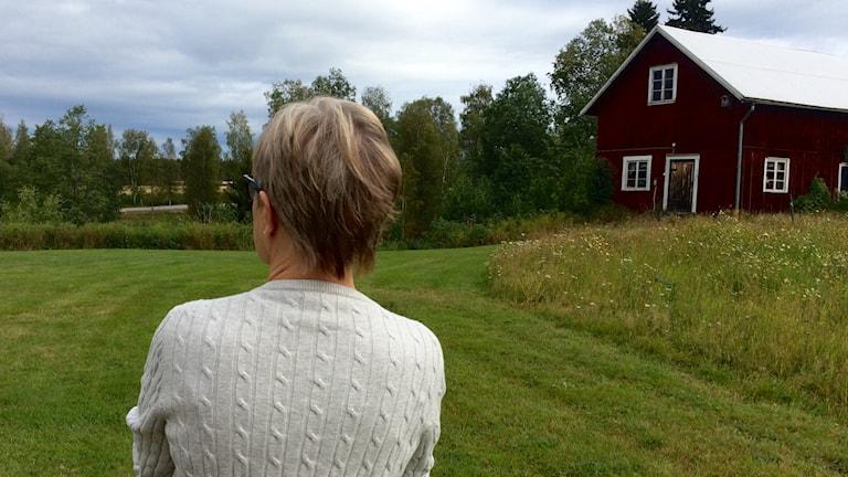 kvinna står på gräsmatta med rött hus och träd i bakgrunden