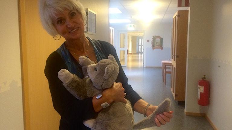 kvinna håller i mjukiskatt i korridor - robotkatt Fatmire Katallozi forshaga demens äldreboende foto: annika ström