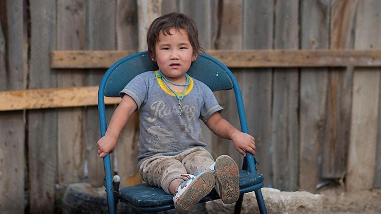 Ett barn sitter på en stol. Foto: Världens Barn
