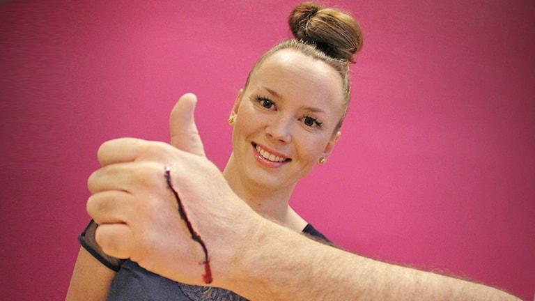Malin Bodin och en hand med ett sminkat sår. Foto: Lars-Gunnar Olsson/Sveriges Radio