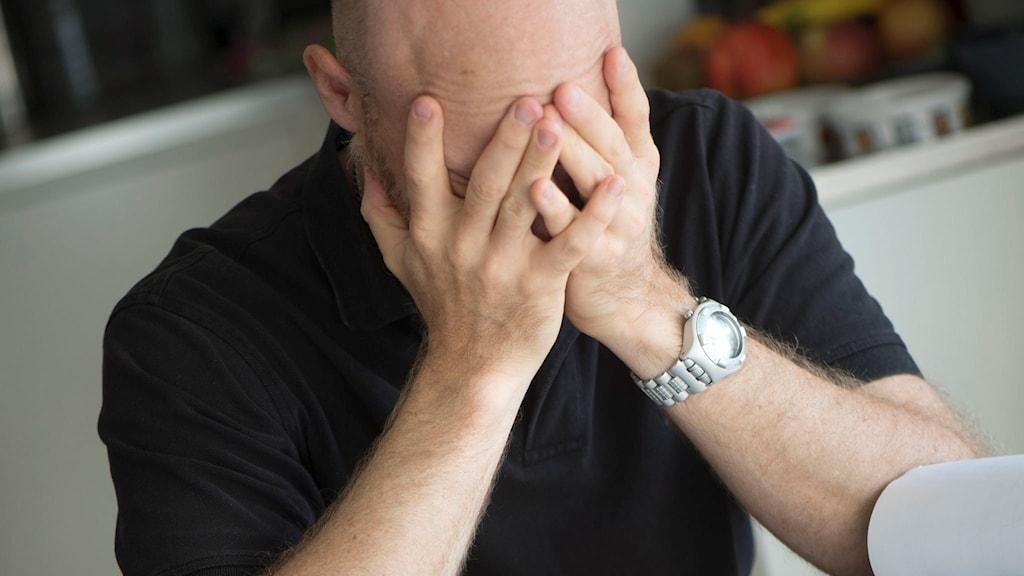 En man med händerna för ansiktet. Foto: Fredrik Sandberg/TT