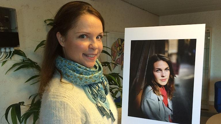 Danspedagogen Ia Pettersson håller upp ett porträtt av jazzsångerskan Isabella Lundgren. Foto: Per Larsson/Sveriges Radio