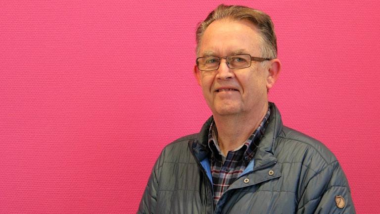 Orföranden i Sunnemo fiberförening Anders Johansson står framför en rosa vägg. FOTO: Louise Gustavsson/Sveriges Radio