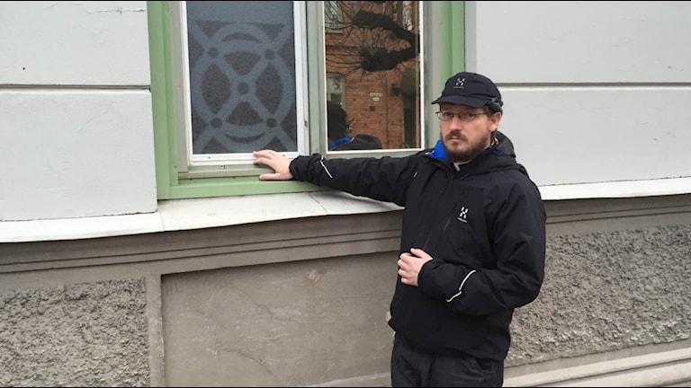 Martin Ferenc, kyrkoherde i Katolska kyrkan i Karlstad visar ett av de fönster som har krossats på en av församlingens fastigheter. Foto: Anton Eriksson/Sveriges Radio P4 Värmland.