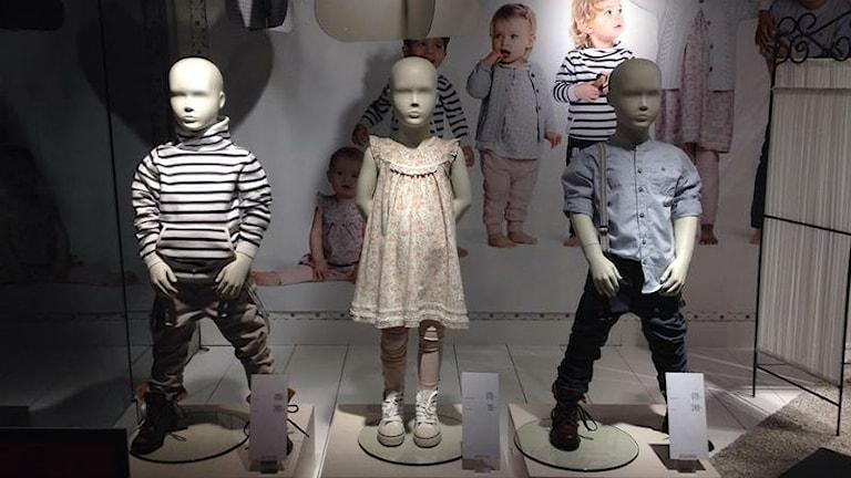Skyltdockor visar barnkläder. Flickan ser undergiven ut, pojkarna ser aktiva och beskyddande ut med benen brett isär.