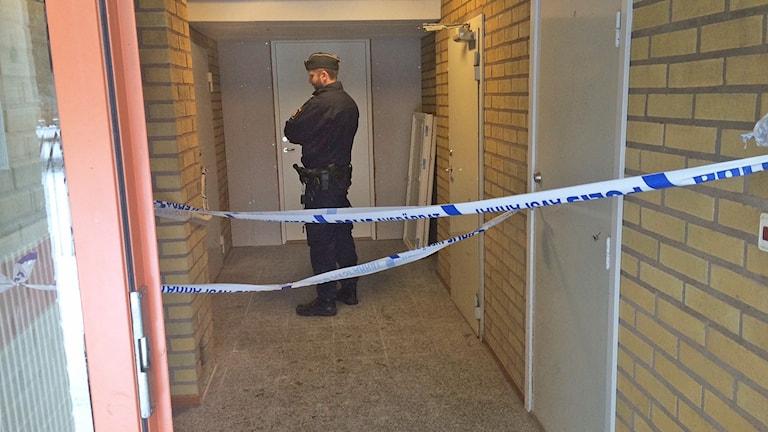 En polis står bakom ett av polisens avspärrningsband. Foto: Jenny Tibblin/Sveriges Radio.