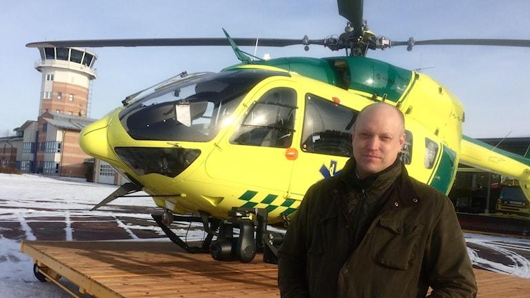 man står framför gul helikopter ute på flygplats