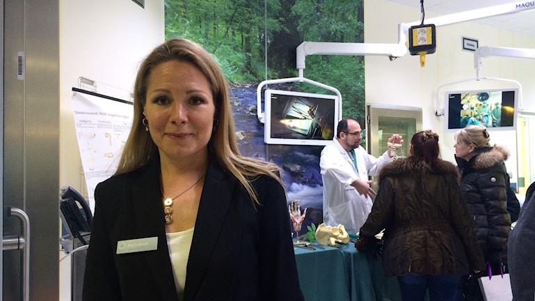 kvinna står i ny operationssal i svart kavaj med besökare ibakgrunden