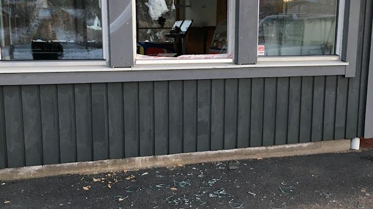 Glaskross på marken framför en kiosk.