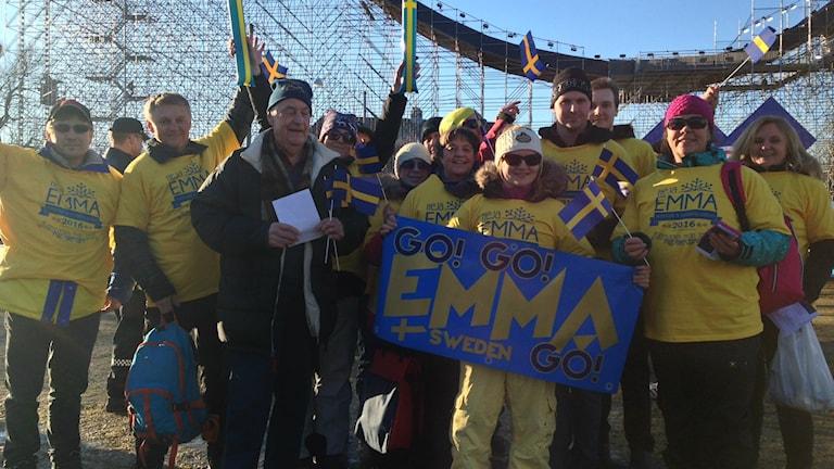 """Gulklädda supportrar med flaggor och en """"Emma""""-skylt"""