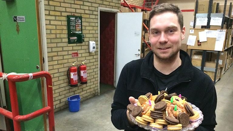 Kristofer Ekengren håller upp ett fat med småkakor och födelsedagsljus.