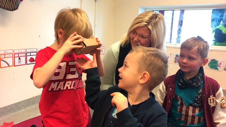 Tre barn som leker med digitala verktyg och en förskolelärare.