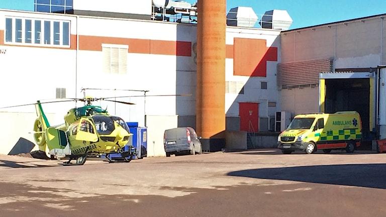 Ambulanshelikopter och en ambulans utanför fabriksbyggnad. Foto: Per Larsson/Sveriges Radio.