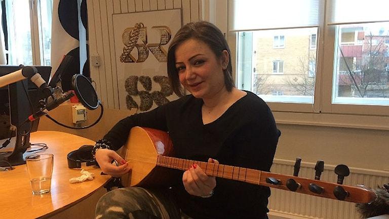 Kvinna med brunt hår spelar på ett stränginstrument