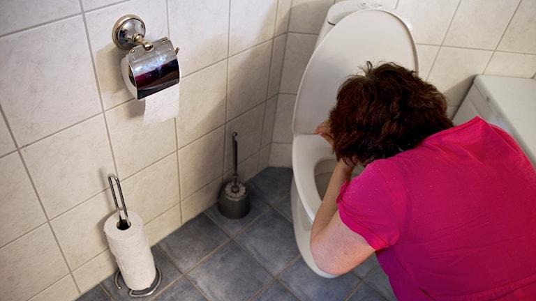 En kvinna hänger över en toalettstol  . Foto: Jessica Gow/TT.