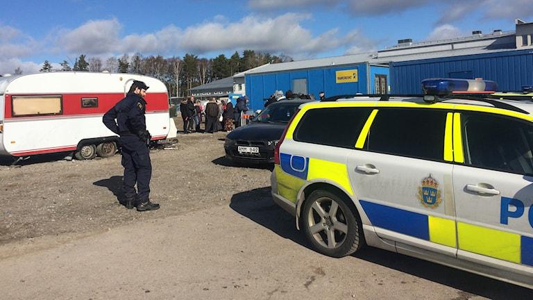 Polisbil vid migrantcamping. Foto: Annika Ström/Sveriges Radio.