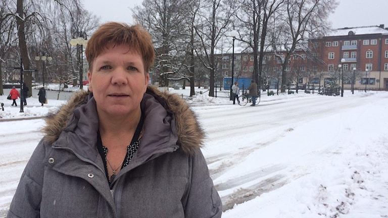 kvinna i grått står ute i snö