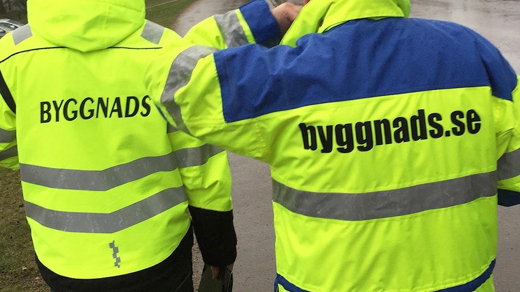 """Två personer vars jackor har texten """"Byggnads"""". Nick Strömgren/Sveriges Radio."""
