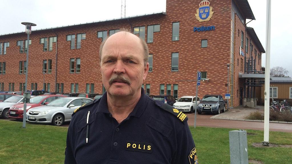 polisman står på gräsmatta utanför polishus