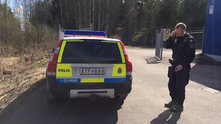 polis utanför polisbil på asfalt framför ett skogsparti