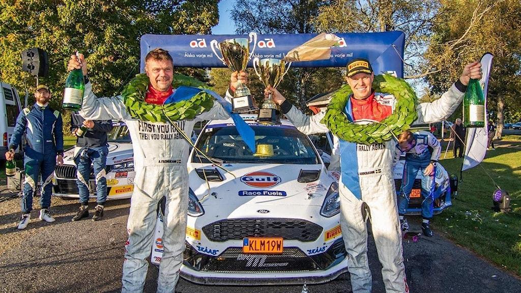 Två män i vita overaller firar vinst med händerna sträckta över huvudet. Foto: Fredrik Värnebjörk