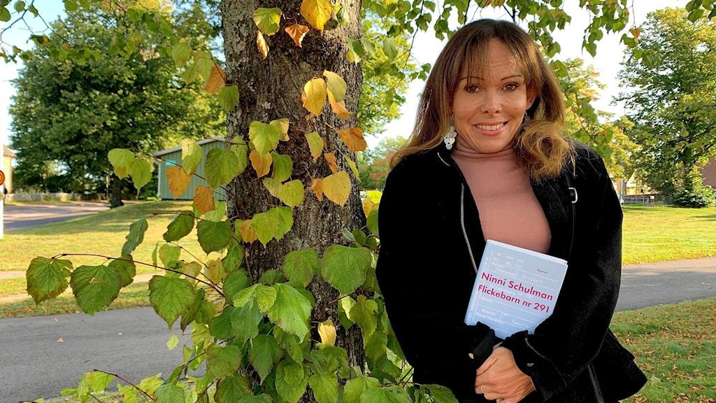 kvinna står vid träd i höstskrud