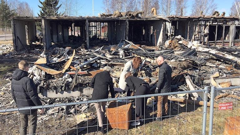 En grupp människor framför en brandhärjad fastighet. Foto: Tomas Hedman/Sveriges Radio.