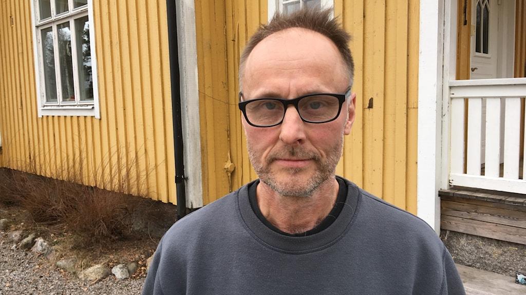 En man i glasögon som står framför ett gult hus.