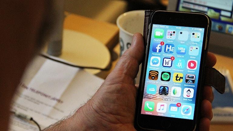 En man håller i en mobiltelefon där man ser många appar. Foto: Sveriges Radio.