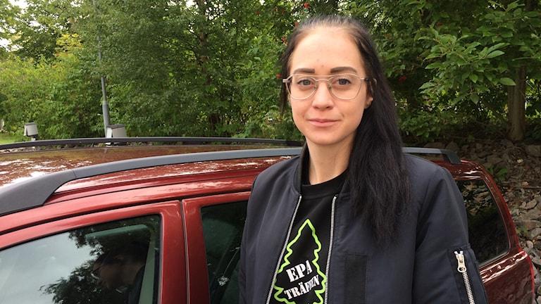 theh med glasögon och svart hår framför bil