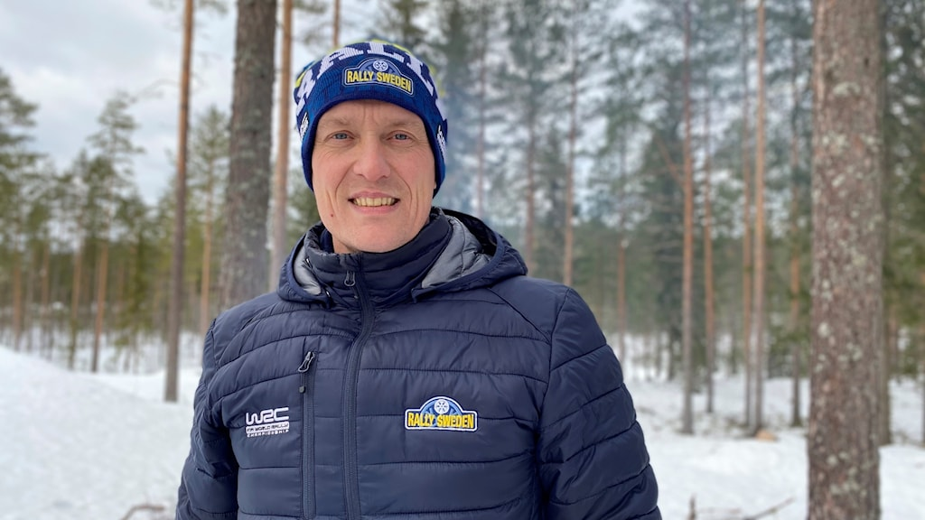 Man med blå dunjacka och mössa som det står Rally sweden på. Står i snölandskap.