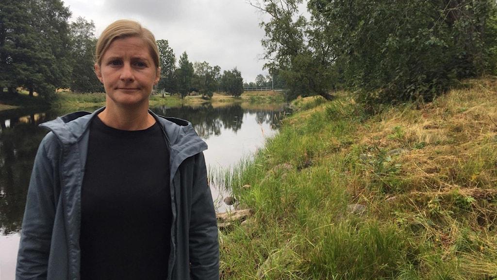 Jenny Monsén, biolog Länsstyrelsen, står vid ett vattendrag.