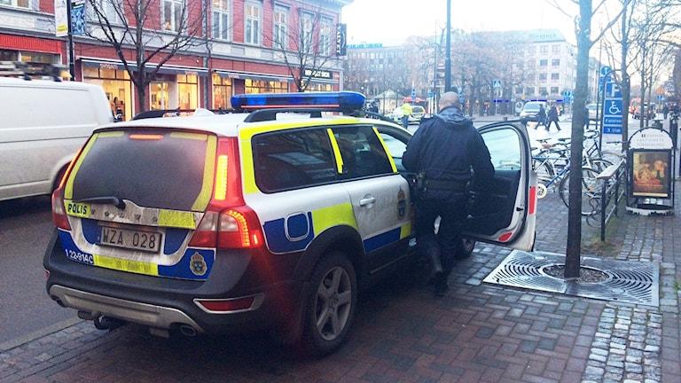 En polis stiger in i en polisbil. Foto: Jenny Tibblin/Sveriges Radio.