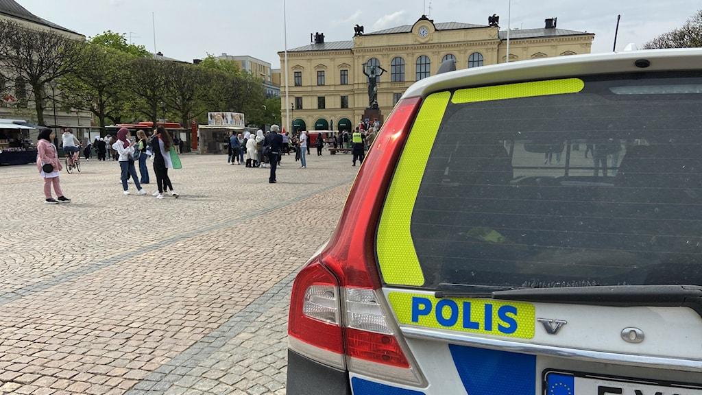 En polisbil i framkant av bilden och ett torg i bakgrunden.