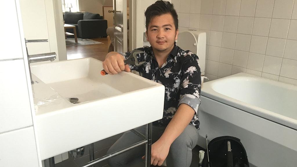 Rohullah Sakhizada, som går vvs-programmet i Karlstad, sitter på huk vid ett tvättställ i ett badrum. Foto: Magnus Hermansson/Sveriges Radio.