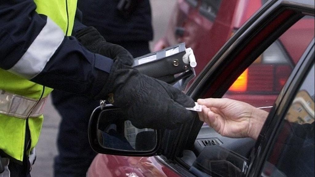 En polis kontrollerar ett körkort i en nykterhetskontroll.