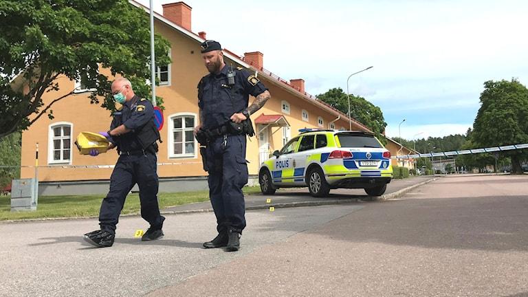 Poliser och en polisbil vid en avspärrad fastighet. Foto: Victoria Svärd Karlsson/Sveriges Radio.