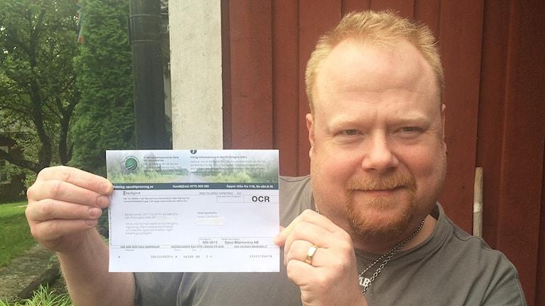 Anders Nordlund visar kostnadsförslaget från ett företag. Foto: Sven Westerdahl/Sveriges Radio.