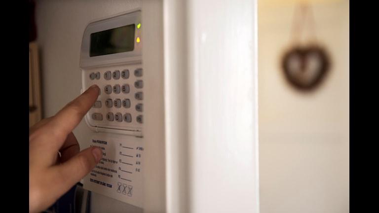 En person larmar på sitt hus med ett villalarm kopplat till sensorer. Foto: Fredrik Sandberg/TT.